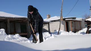 Young man shoveling and removing snow in front of her house in the suburb.