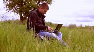 Young man sitting on the grass is working on laptop. Concept freelancer working sitting in the park.