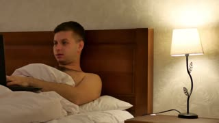 Young man working on laptop on bed in hotel apartment in the evening.