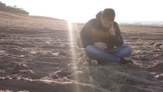 Young man working outdoors with tablet. Man using a tablet computer outside at sunset.