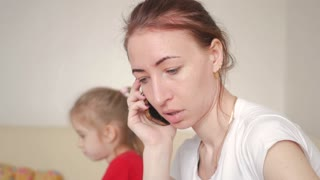young mom talking mobile phone at home