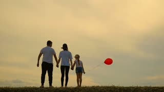 Young mother and father with daughter are laughing and playing with balloon on meadow at sunset background. Happy loving family is having fun on nature in the summer.