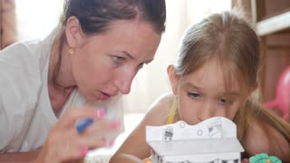 Young mother and her beautiful daughter, paint a paper house, lying on the floor at home, lifestyle, creativity, education.