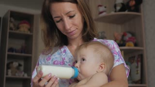 Young mother feeding her baby son with a bottle of milk at home.