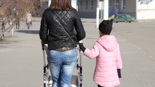 Young mother walking with daughter outdoors in a spring park pushing pram.