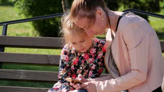Young mother with daughter relaxing outdoor. They sitting on the bench playing with smartphone at the park. A young woman holds a baby girl on her lap.