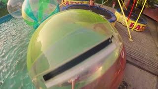 Young pretty girl playing inside a floating water walking ball, zorbing, aquazorbing
