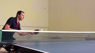 Young sports man table tennis player in play on old gym. Action shot.