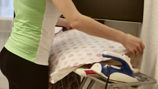 Young woman ironing cloth with steaming on the iron board in the living room at home.