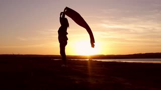 Young woman silhouette at sunset, manage cloth at sunset