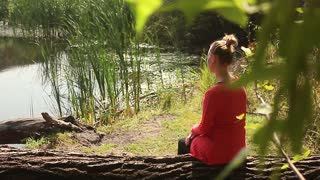 Young woman sitting on a tree by the lake.