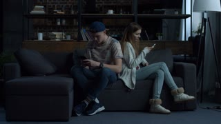 Attractive young couple sitting back to back at home on couch obsessed with smartphones. Couple with mobile phones ignoring each other as strangers, communication problems and social network addiction
