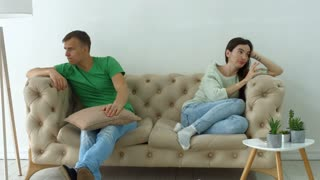 Beautiful couple not talking after quarrel on the sofa in domestic room. Adult married couple having difficulties in relationship ignoring each other while sitting on the couch after a dispute at home