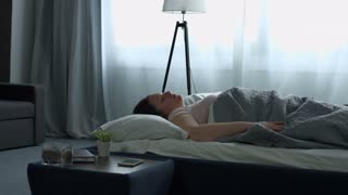 Charming middle aged long brown hair woman in pajams waking up with mobile alarm clock and stretching her arms in the bed in the morning. Yawning plus size female stretching in the bed after awake.