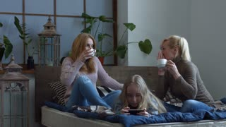 Cheerful middle aged women siting on the bed with mugs of coffee and gossiping while confused little girl playing on smart phone in bedroom. Two joyful women chatting and telling secrets over coffee.