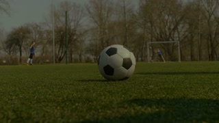 Closeup of soccer player's foot kicking ball. Low section. Young footballer preparing for free kick and hitting soccer ball with his foot over teammates doing football training session background.