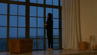 Dreamy thoughtful young asian woman looking out the wide window and thinking. Full lenght. Silhouette of beautiful brunette female standing near window and looking at city view in the evening at home