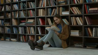 Gorgeous college female student reading a book in campus library while sitting on the floor. Confident young blonde woman studying hard and preparing for the exams in university library