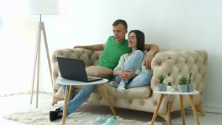 Joyful millennial couple streaming video content on line using laptop pc while sitting comfortable on the sofa in domestic room. Smiling positive couple watching tv show online on notebook pc at home.