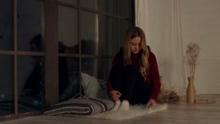Sad gorgeous long blonde hair girl looking out the window in the evening at home. Depressed young charming woman waiting for a call and checking phone while sitting alone on the floor near big window