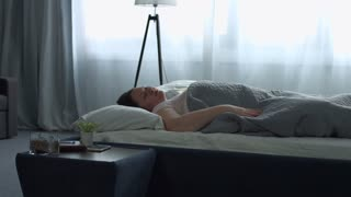 Sleepy adult woman snoozing alarm clock on smart phone and sleeps covering her head and ears with pillow in the morning. Tired female covering her ears with pillow while alarm clock on phone ringing.