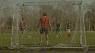 Young football team exercising, passing and shooting on goal during football training session on soccer pitch. Positive soccer players playing football on sports field.