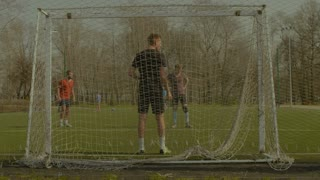 Young goalie failing to save goal after shot from penalty area during football training. Goalkeeper is unable to stop the soccer ball into goal while team practicing football session on the pitch.
