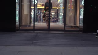A beautiful woman in a dress comes out of the store through a sliding glass door