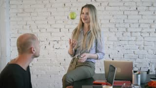 A business woman throws a green apple and a man catches him at the office. Coworkers an informal setting in office