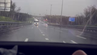 A car with headlights on goes after another car on the highway. Back view