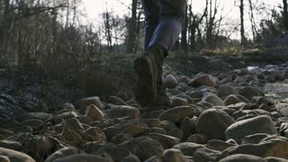 A female in stylish military boots walks the stones. A bank of the river with big gray stones. Slow motion