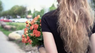 A girl walking with a bouquet of roses along the street