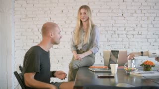 A guy throws a green apple and a business girl catches him at the office. Coworkers an informal setting in office