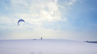 A man is engaged in snow kiting on a snowy hill in winter, jumping and enjoying. An athlete is steering his parachute