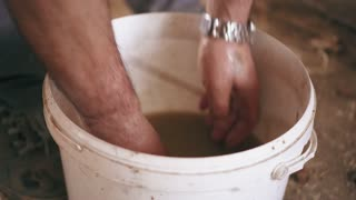 A man is washing hands ina dirty water from the bucket after finishing work