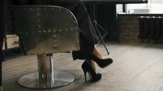 A woman in beautiful shoes sits in a barber chair. Legs close up view