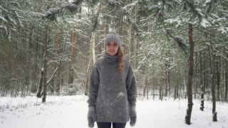 A young girl stands in the forest and facing camera. Snow falling in slow motion. Snowstorm. Slow mo