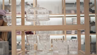 A young hipster female in fashion glasses chooses beautiful home acessories in the store. Shopping