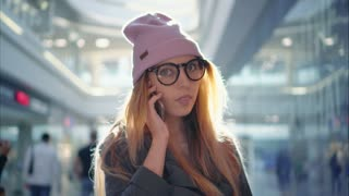 A young hipster female is talking on the phone in the big mall
