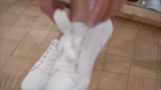 A young woman ties up her shoelaces on white sneakers in a store. Close-up