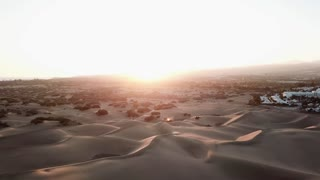 Aerial: beautiful landscape of a desert with sand dunes in sunset light. The sun is setting in a desert, camera flies down. Gran Canaria