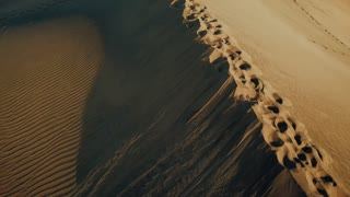 Aerial view on a line of human footprints on sand dunes in a desert. Beautiful woman in light pink dress is laying on a sand in a hot desert in sunset light. Gran Canaria