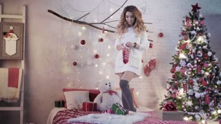 An attractive girl in mittens dancing on a bed next to a Christmas tree and breaks the decoration