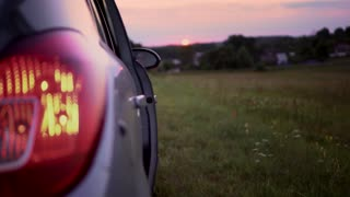 An attractive girl opens the car door and leaves at sunset