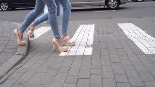Attractive legs in high heels walking across the street in the city