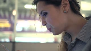 Attractive smiling woman using smartphone in cafe. Close-up hands and eyes. Dolly shot