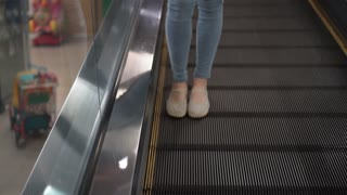 Attractive woman moving down an escalator at the mall