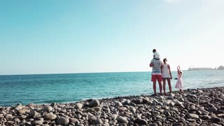 Beautiful family of four is standing on a coastline and staring the ocean and clear blue sky. Summer travel vacation for family in Gran Canaria.