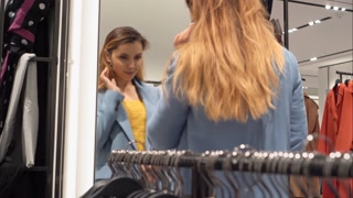 Beautiful girl trying on a new jacket near the mirror in the store