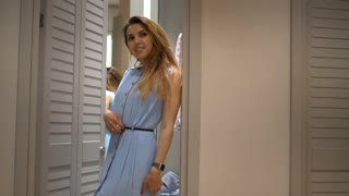 Beautiful happy woman try on new dress in dressing room